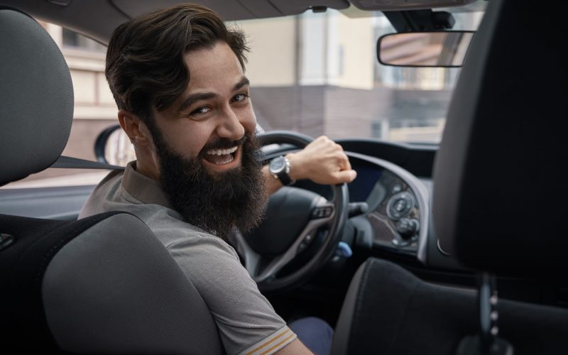 Riding his new car. Side view of handsome young bearded man driving his car and smiling, in the city