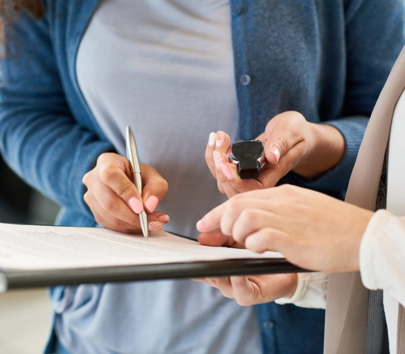 Close-up shot of unrecognizable customer holding car key in hand and signing contract after successful deal in automobile showroom, consultant assisting her